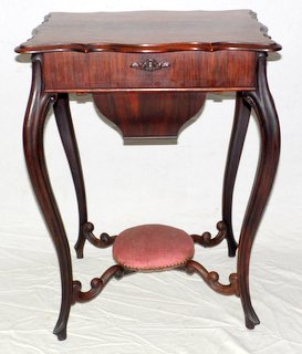 Good Victorian Rosewood Work Table .19th Century. The shaped molded top opens to reveal a well fitted storage area over a pull out compartment.Supported on cabriolet legs linked with a circular upholstered  foot rest.  Height 25 1/2in.Width 22 1/2 in.  Depth 17 1/2 in.