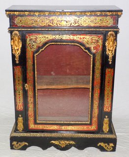 A Late 19th Century Ebonised French Boulle Pier Cabinet .Having decorative cut brass inlaid in red tortoiseshell panels framing the single glazed door. All supported on a shaped plinth base.  Height 45 in.Width 32 in.  Depth 12 in.