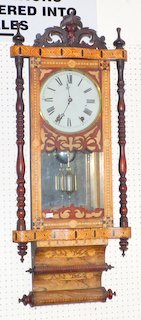 Jerome & Co's Anglo-American Mahogany and Marquetry Inlaid Wall Clock c.1900. Having an 8 inch White Painted Dial with Roman Numerals and Pendulum Driven Movement Striking on the hour, Paper Advertising Label on the back. 38 inches Tall (working order)