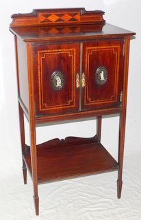 Edwardian Sheraton Revival Inlaid Mahogany Music Cabinet. Early 1900. The shaped  and moulded upstand back over 2 doors with carved bone classical figure roundels, geometric inlays opening to reveal a shelved interior. Below the undershelf with shaped upstand  all supported on tapered legs with spade feet.   Height 43 in.  Width 23 in.  Depth 16 in.