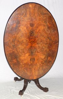 Victorian Burr Walnut Oval Breakfast Loo Table Tilt Top. Late 19th Century. Fine carved walnut base with period brass and ceramic castors.   Top 53 x 38 in.  Height  30in.