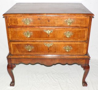 An English George II Walnut Three Drawer Chest. Mid 18th Century. The moulded top with bookmatched veneers and herringbone crossbanding over 3 drawers with matching veneer work to the top and mounted with brass swan neck handles and escutcheons. Standing on a shaped plinth base with cabriole legs on hoof feet.  Height 34 in.  Width 34 in.  Depth 23 in.